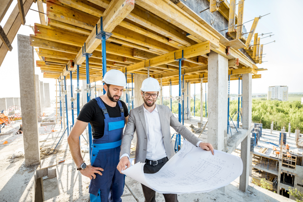 pracownik budowlany oraz projektant analizują proejkt domu na budowie