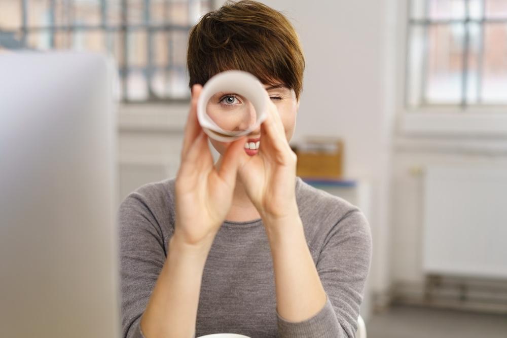 patrzenie przez rulon kartki przez kobietę