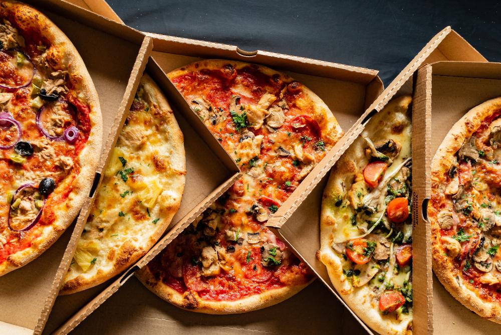 kilka pizz w kartonach na stoliku